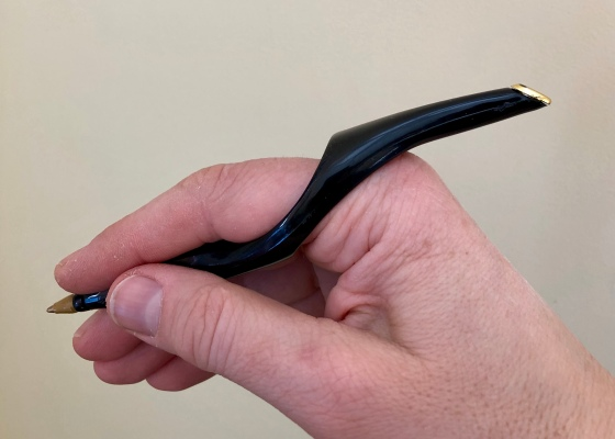 A hand holds the RinG-Pen with forefinger inserted through ring. Pen extends in either direction from the base of the forefinger.
