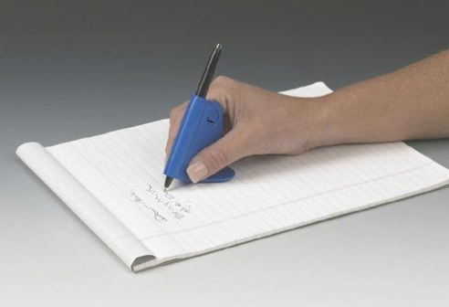A hand writing on a notepad with a pen attached to a plastic support that folds around the pen and spreads out under the hand to stabilize against the writing surface.