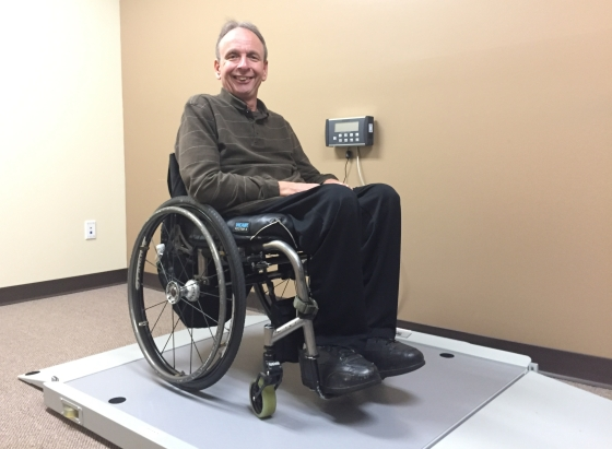 Smiling man in manual wheelchair on a roll-on scale in a small room.