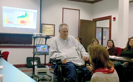 A man in a power wheelchair in a conference room talking with a woman kneeling before him. Behind him is a projected image of a pressure map showing a red hot spot. There are clinicians observing seated on the photo's perimeter.