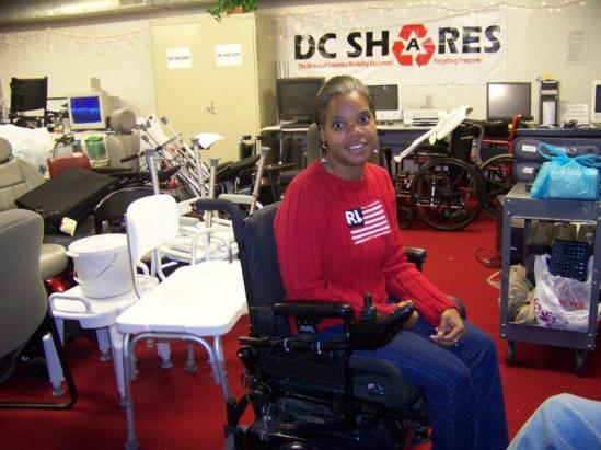 A young woman seated in a power wheelchair smiling in a room full of durable medical equipment. A banner behind her reads DC SHARES: the District of Columbia Disability Equipment Recycling Program.