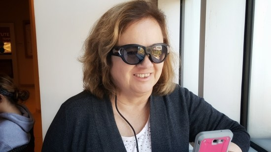 A woman wearing dark glasses with a cord hanging down, holds a smartphone smiling.