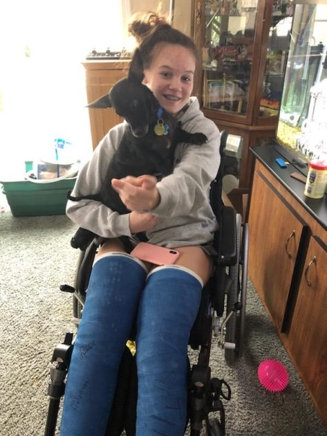 A girl with two broken legs, casts above the knees, seated in a wheelchair smiling with a small dog on her lap.
