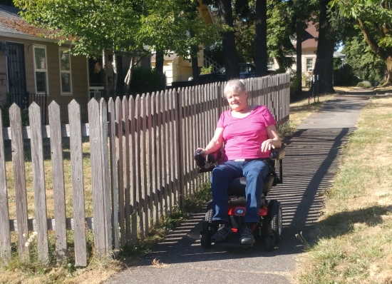 An older woman travels a sunny sidewalk along side a picket fence in her power wheelchair smiling.
