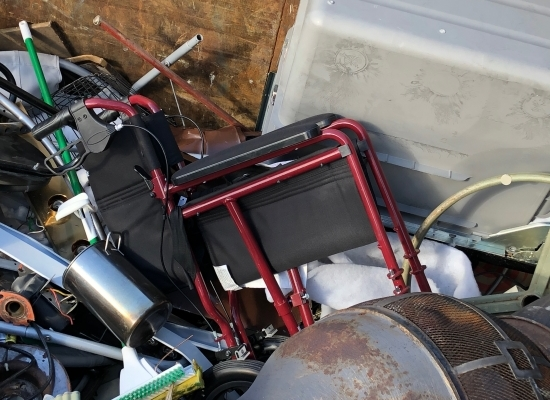 A new transport wheelchair in a heap of scrap metal garbage.