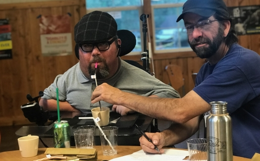 A man in a power wheelchair receives assistance from another man to sip from a straw and take notes. there are a variety of cups and straws on a table before him.