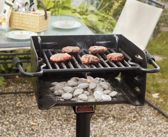 A grill on a post with a grate and side handles. Burgers are cooking above burning briquettes.