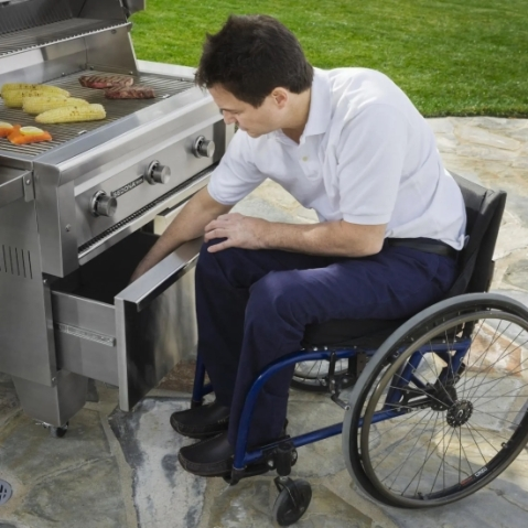 A man in a manual wheelchair reaches into a deep drawer under a gas grill.