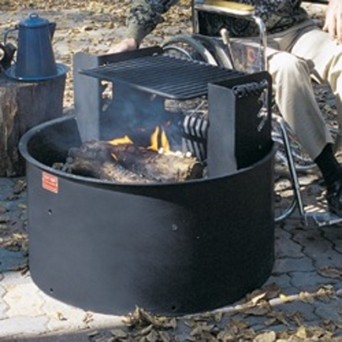A deep metal fire ring burning wood with a mounted grill grate. A person is seated in a wheelchair behind the grate.