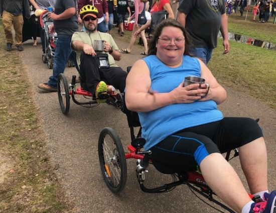A man and a woman seated in recumbent trikes, the woman in front and smiling broadly. They are outdoors on a path with a crowd of people behind them.