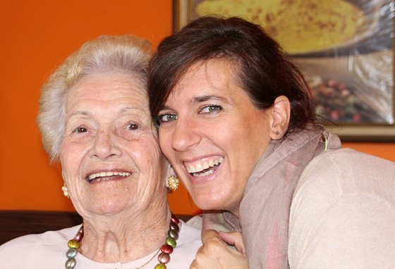 Head-shot of two women smiling for a selfie, embracing; one is elderly.