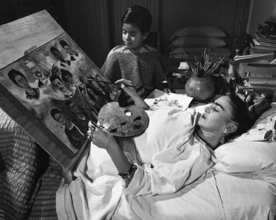 A woman painting a picture from a prone position in bed using a slanted easel and palette.