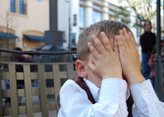 Young boy with hands over face in shame.