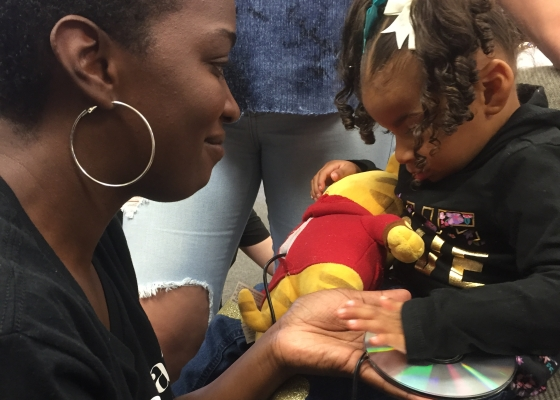 A little girl holding an adapted toy animal presses a CD switch to activate it while her mother looks on smiling.