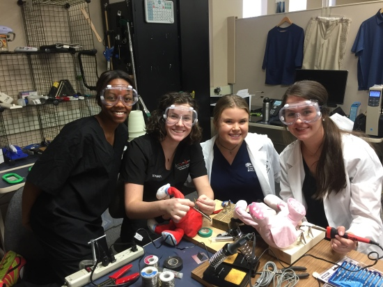 Four young women working at a workbench with soldering irons and plush toys smile for the camera.