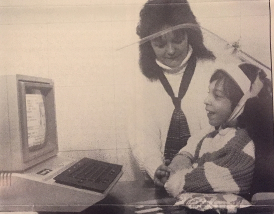 A little girls wearing a head pointer smiles at an early desktop computer. A woman stands beside her.