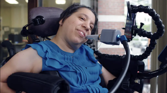 A smiling woman seated in a power wheelchair mounted with a smartphone and mouth-controlled joystick controller.