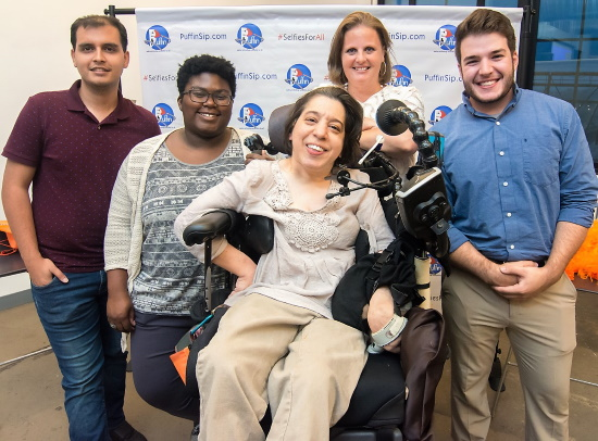 A smiling woman in her power wheelchair with two men and two women standing smiling with her.