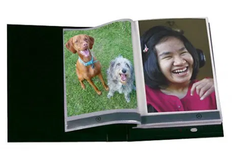 A photo album open displaying a picture of dogs and a picture of a girl.