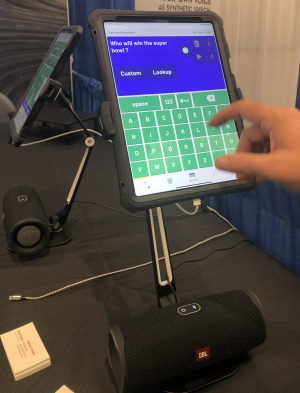 A tablet displaying an AAC app with text keyboard is mounted with a barrel-shaped external speaker at its base. A hand is making letter selections to ask Who will win the superbowl?