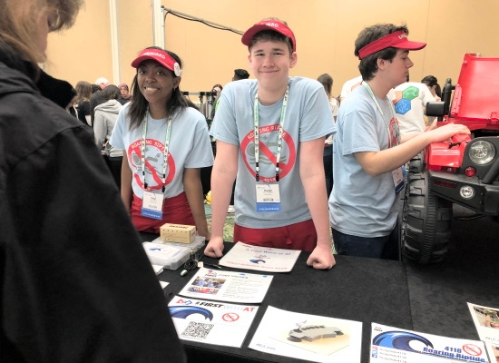 Two smiling members of the Roaring Riptide robotics team of Florida University, an African-American young woman and a Caucasian young man. An additional teammate stands to the side working on a large toy car. All are behind a display table in an expo hall.