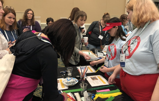 A crowd of women wait and build at a maker station in an expo hall while two young women assist wearing their team t shirts.