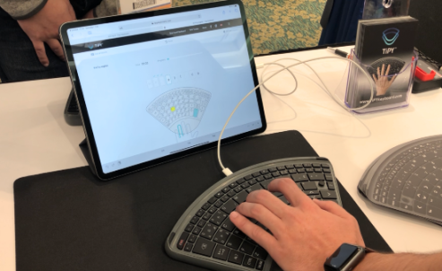 A sleek flat wedge-shaped keyboard with wrist support and keys that fan out above like concert seating. A man's hand is typing with the aid of a tablet and app that demonstrates which finger to use for specific letters and functions.
