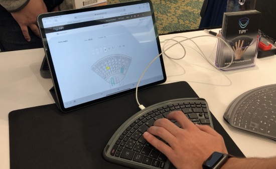 A wedge-shaped one-handed keyboard with a hand typing before a tablet displaying learn software.