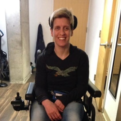 A woman seated in a power wheelchair smiling.