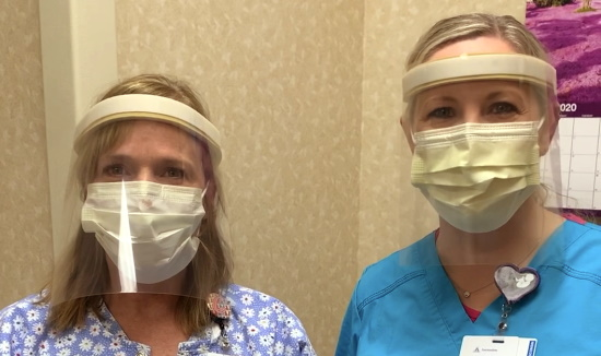 Two women in scrubs wearing surgical masks and plastic face shields.
