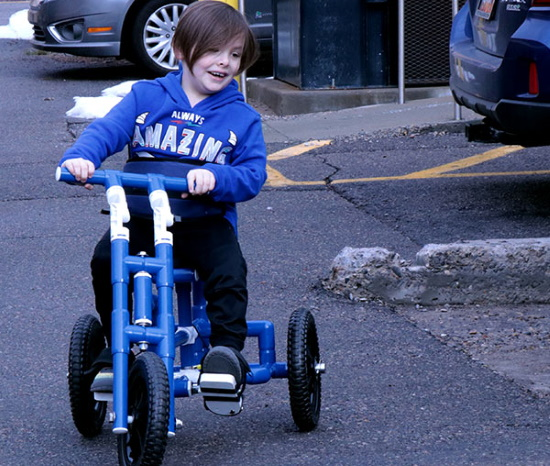 Smiling young boy on a PVC-built trike peddling in a parking lot.