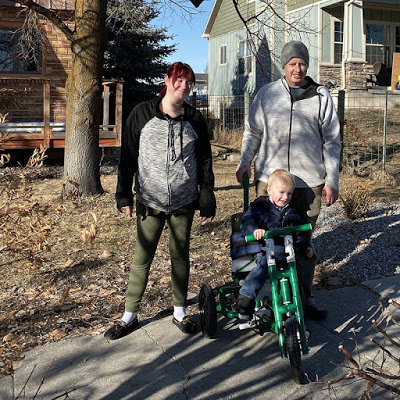 A couple with their young son on a PVC-built trike outside their suburban home.