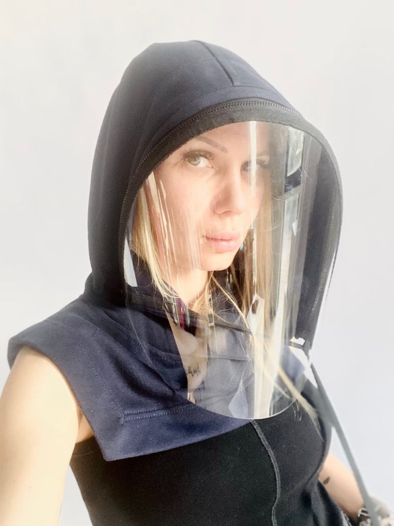 A woman wears a hooded face shield that drapes around her shoulders.