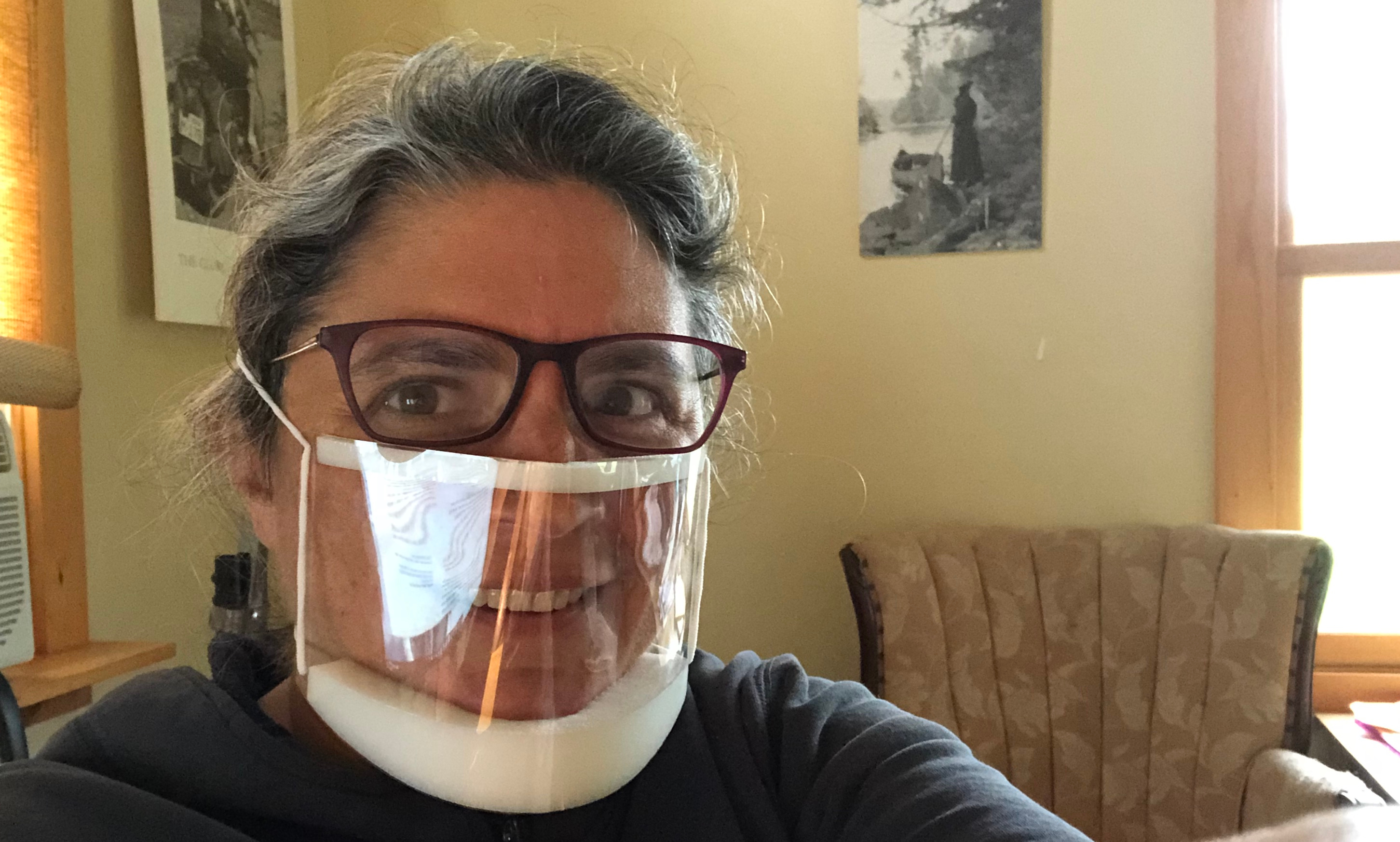 The author smiles wearing a clear mask that is pushing her glasses high on her face and showing considerable glare.