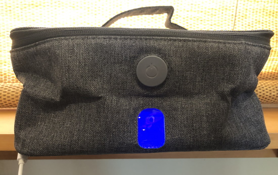A grey box-shaped cloth bag with a glowing window, power button, and handle.
