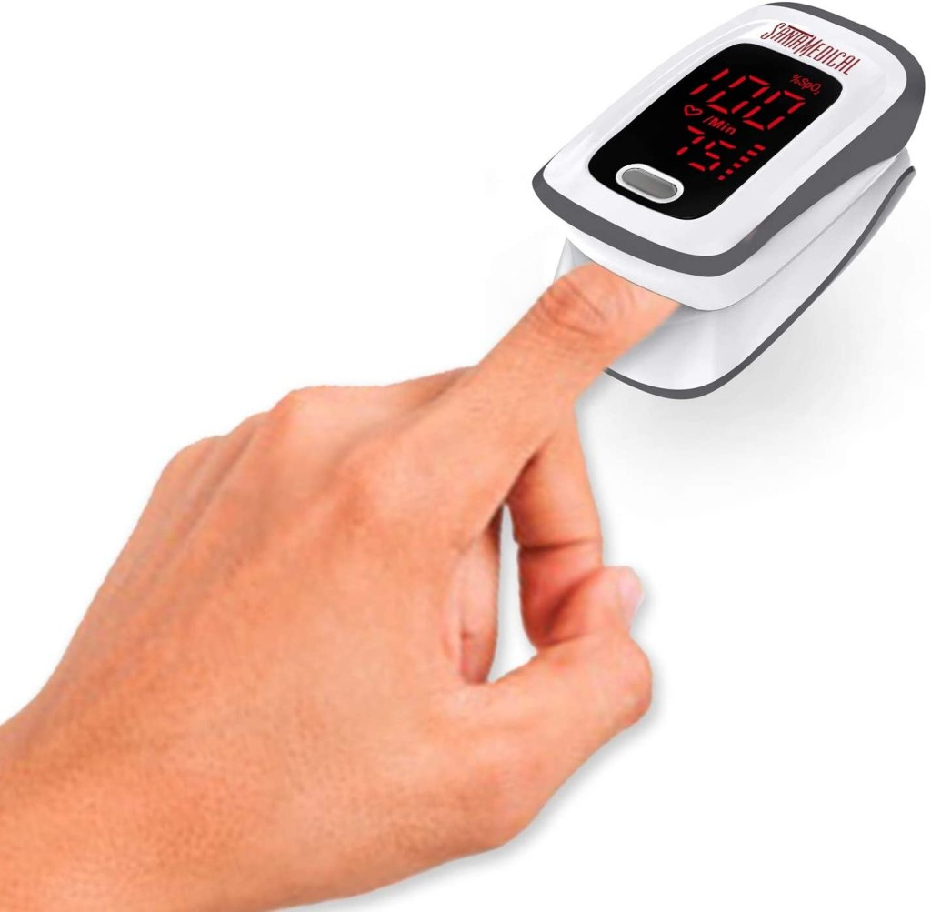 A hand with its forefinger resting in a pulse oximeter with an LED display.