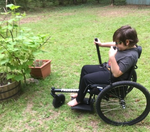A boy operates the hand levers of an all-terrain wheelchair in a yard with a vegetable garden.