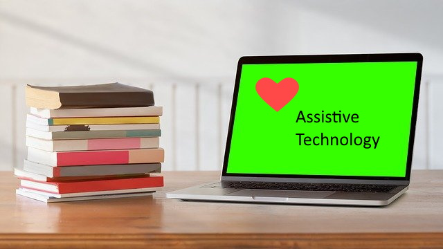 "A stack of books on a table with an open laptop displaying a heart and the words ""assistive technology"""