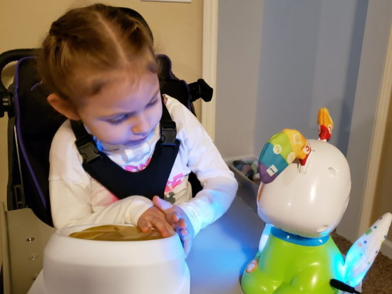 A young girl activating a switch-adapted toy.