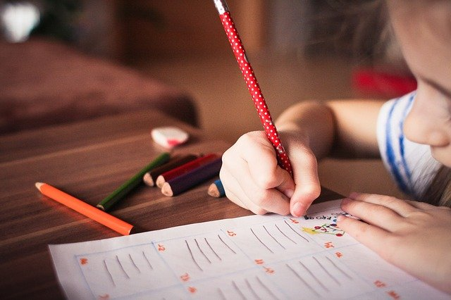 Child writing with colored pencils at desk.