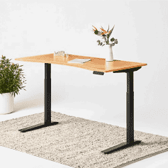 A height-adjustable desk with a vase of flowers.
