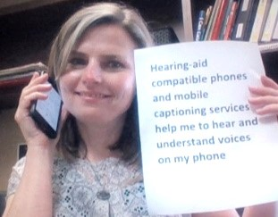 A woman holding a mobile device to her ear holds a sign that reads, Hearing-aid compatible phones and mobile captioning services help me to hear and understand voices on my phone.