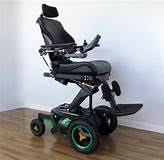 A power wheelchair with a seat elevator and head support.