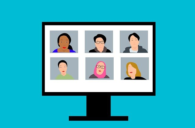 Monitor displays six people of diverse ethnicities video conferencing.