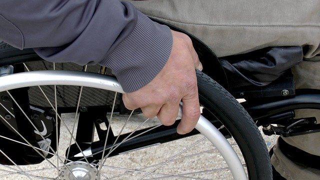 Close-up of a hand grasping the wheel and rim of a wheelchair by the seated chair user.