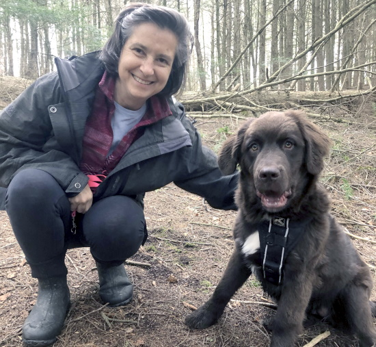 A woman smiles for the camera while crouching next to her puppy in the woods.