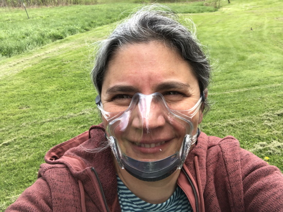 A woman wearing a clear form-fitting face mask outdoors.