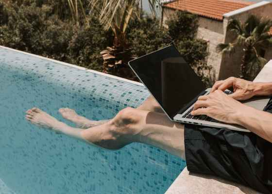 Crop photo of man dangling his legs into a swimming pool while using a laptop.