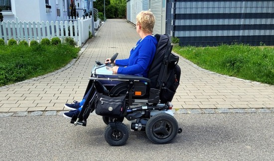 A woman traveling in a power wheelchair on pavement in a residential community.