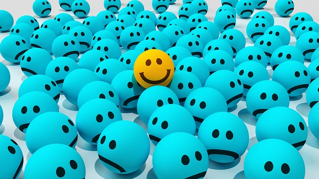 A crowd of blue sad emoji faces (like rubber balls) with one yellow smiling emoji rising from the group's center.